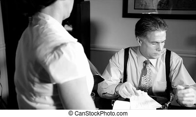 A scene set in the 1940's taken over the shoulder of a woman talking to a man sitting behind a desk who appears troubled by what she is telling him. Black and White, film Noir,