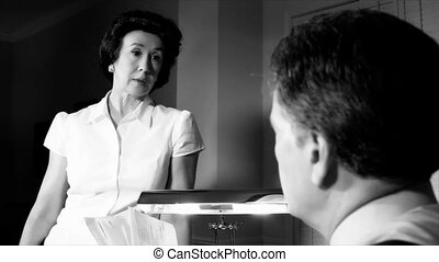 An annoyed then sympathetic or troubled woman dressed in 1940's style stands talking to a man sitting at a desk in front of her. Black and White. Film Noir Genre