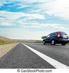 noir, voiture, dans mouvement, sur, asphaltez route, bleu, ciel, à, nuages