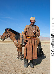 Nomad with his faithful horse in the steppes of Mongolia