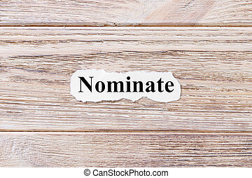 NOMINATE of the word on paper. concept. Words of NOMINATE on a wooden background