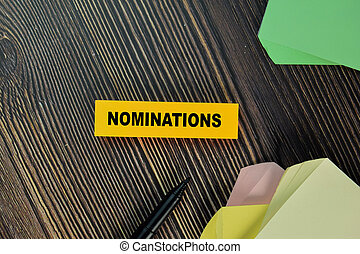 Nominations write on sticky note isolated on Wooden Table.