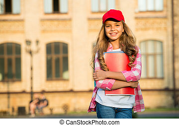 Non-formal education. Happy child hold books in schoolyard. School library. Casual fashion style. Non-formal learning. A new education perspective, copy space.