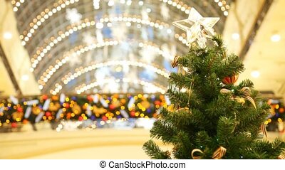 non-natural tree with bows and star at top against roof of shopping centre