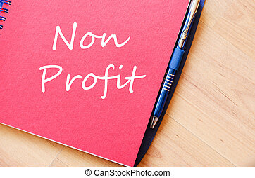 Non profit text concept - Red notepad and Non profit text...