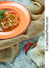 Noodle and beef soup on a light gray textured background. Beautiful serving dishes. Restaurant menu
