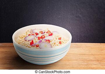 Noodle in bowl on dark wooden background