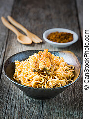 Noodle in ceramic bowl with dried fish on wooden background.