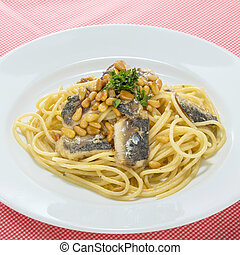 Noodle pasta with sardine fish on white platter