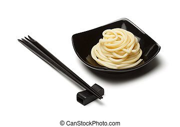Noodles in black ceramic dish stand isolated on white background with chopsticks and rest near.