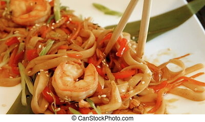 Noodles with shrimp and fryed vegetables. Eating asian food with chopsticks