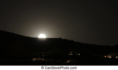 Norco Moonrise - A moon rising over a residential hill in...