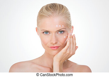 blond woman testing cream on her cheekbone and her front on grey background