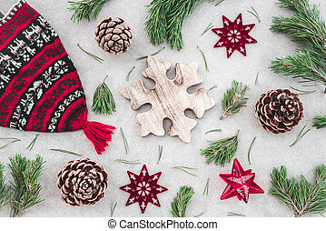Nordic style Christmas decor. Red knitted winter hat, green pine branches, cones and stars, on concrete background.