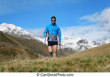 Nordic walking in the mountains a young man