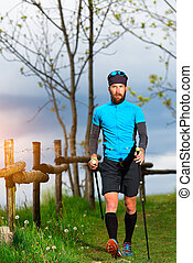 Nordic walking of a man near a wooden fence