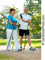 Nordic Walking - senior couple nordic walking in the park