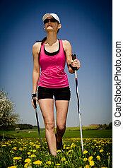nordic walking - a young woman making nordic walking....