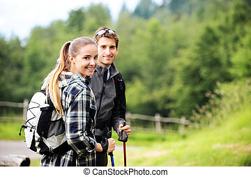 Nordic Walking - Young cheerful couple enjoying a nordic...