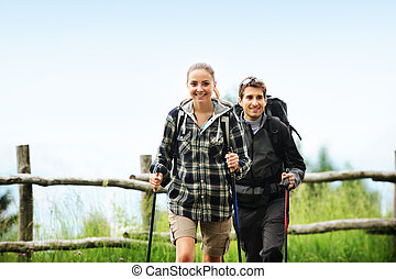 Nordic Walking - Young cheerful couple enjoying a nordic...