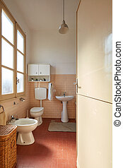 Normal bathroom with pink tiles in old apartment interior