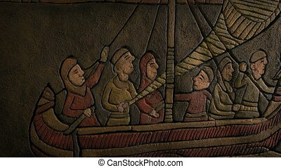 Circling around old carved artwork of Nordic ship sailing