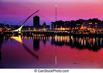 North bank of the river Liffey at Dublin City Centre at night with Samuel Beckett Bridge and The Spire as seen from the south bank