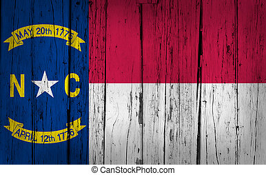 North Carolina grunge wood background with North Carolinian State flag painted on aged wooden wall.
