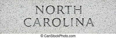 North Carolina state name written in grey granite stone