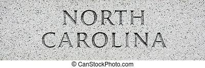 North Carolina state name written in grey granite stone