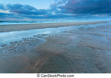 North sea coast at low tide in dusk