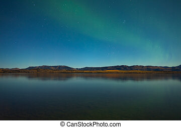 Northern lights and fall colors at calm lake