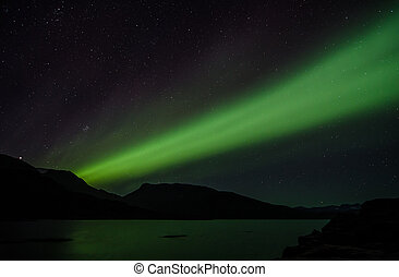 Northern lights at night over a lake in Igaliko