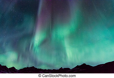 Northern Lights dance over the mountains.