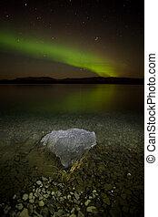 Intense northern lights (Aurora borealis) over Lake Laberge, Yukon Territory, Canada, with rock on lake shore.