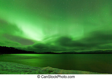 Green sparkling show of Aurora borealis or Northern Lights on cloudy night sky winter scene of Lake Laberge, Yukon Territory, Canada