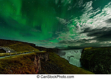 Aurora Borealis in an amazing nightscape. Travel destination with beautiful green lights landscape.