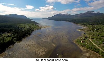 Northern river flows into the sea. The span of the drone over shallow water against the backdrop of mountains