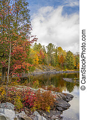 Fall colors line a northern river in autumn - Algonquin Provincial Park, Ontario, Canada