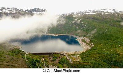 Norway. beautiful landscape of Norway. clouds and fog over the lake in the background of mountains and forests.