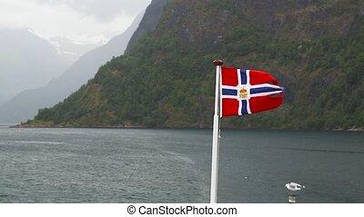 Norway flag waving on background of fjord Norway - Norwegian...