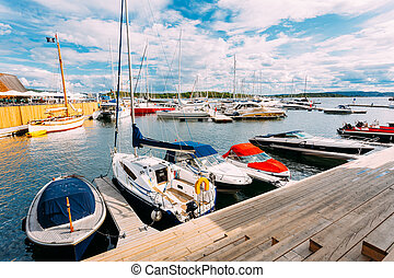Norway, Oslo, Aker Brygge District. Wooden Sea Pier With Moored Boats