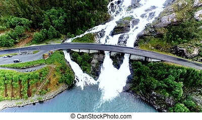 Aerial footage of Langfossen waterfall in Norway and road bridge with cars passing above the waterfall.