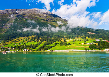 Norwegian village landscape with turquoise fjord water, mountains and colorful houses