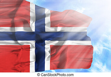 Norway waving flag against blue sky with sunrays