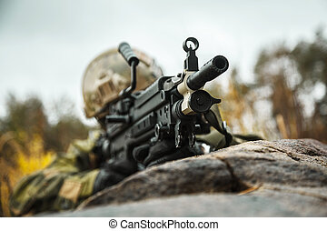 Norwegian Rapid reaction special forces FSK soldier firing in the forest. Field camo uniforms, combat helmet and eye-wear goggles are on