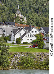 Norwegian traditional village, river and hill. Norway rural landscape