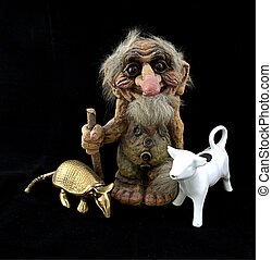 Norwegian troll figurine with walking stick and porcelain cow and brass armadillo