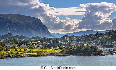 Norwegian village in fjord landscape on sunny day