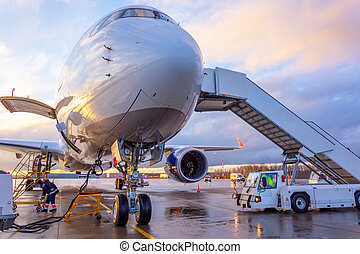 Nose view of an airplane with gangway for boarding parked at an airport during sunset bright light shine and clouds in the sky.
